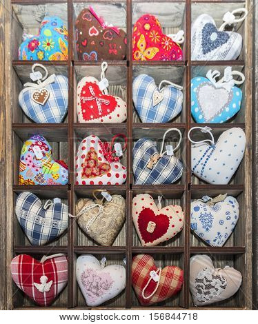 ColmarFrance- December 62013: Colorful heart shape pin cushions souvenirs are in a wooden box on a Christmas market stall in Colmar Alsace France on December 62013.