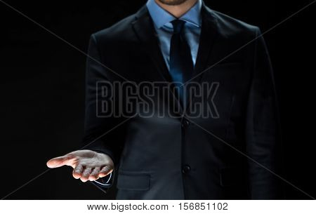 business, virtual reality, people and advertisement concept - close up of businessman in suit holding something imaginary on palm of his hand