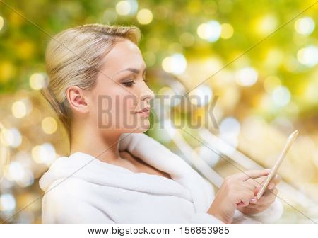 people, beauty, lifestyle, technology and relaxation concept - beautiful young woman in white bath robe with smartphone social networking at spa over holidays lights background
