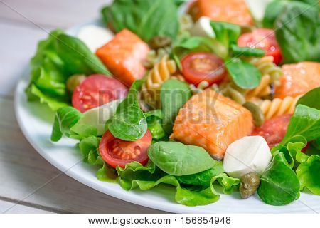 Salad With Fresh Vegetables And Salmon On Old Wooden Table