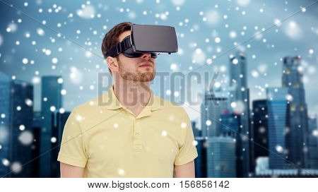 technology, augmented reality, winter, christmas and people concept - young man with virtual headset or 3d glasses over singapore city skyscrapers background
