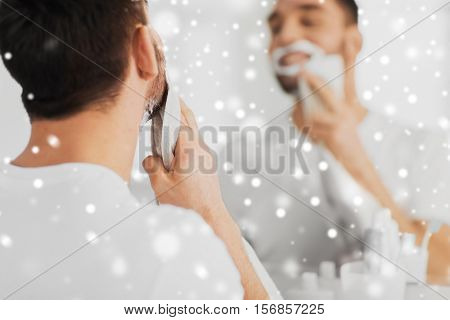 beauty, shaving, grooming and people concept - close up of man removing shaving foam from face with towel and looking to mirror at home bathroom over snow