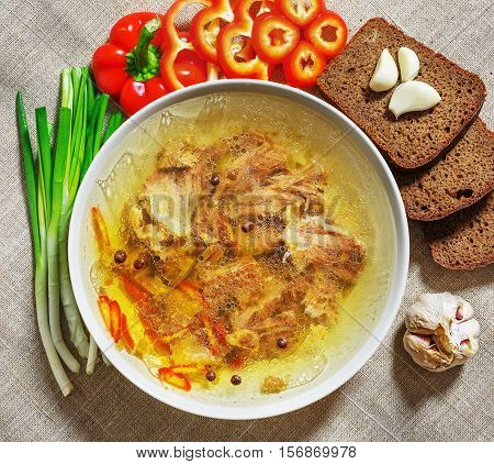 broth with meat or soup in a bowl, bread, pepper, garlic and green onion, top view