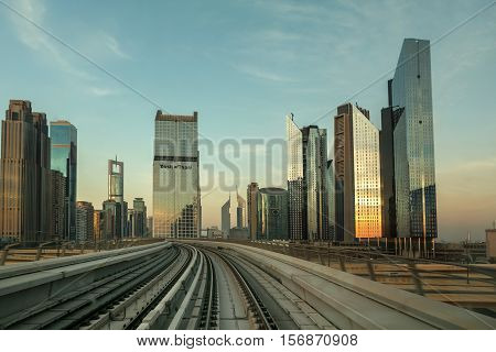 DUBAI UAE - NOVEMBER 9 2016: Burj Khalifa skyscraper is tallest in the world. Colorful sunset time. View from train - metro Dubai. Panorama of skyscrapers in Dubai in the evening sun. Photo shoot of a subway train.