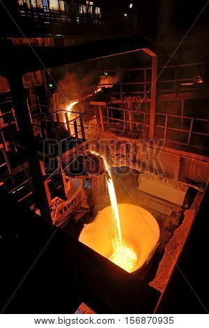 pouring molten steel in steel ladle, close up