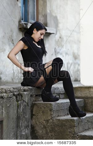 punk girl dressed in black, is sitting on the stairs