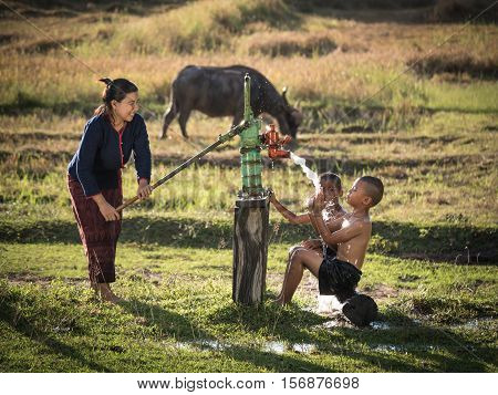 Mother her sons shower outdoor from Groundwater pumpAsian woman and little boys Countryside Thailand.
