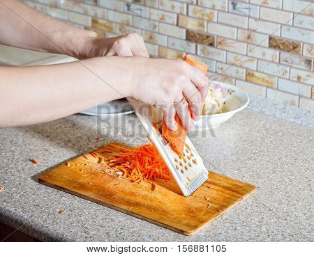 woman cooks the carrot on a grater hands closeup