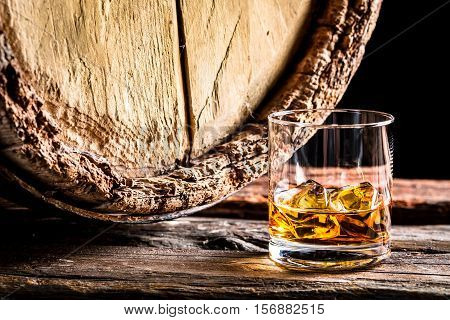 Whiskey Glass And Old Oak Barrel On Black Background