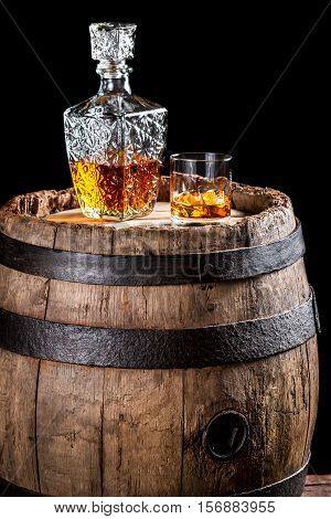 Glass Of Golden Aged Brandy Or Whiskey And Old Oak Barrel