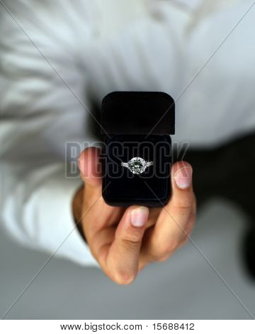 A man proposing and holding up an engagement ring