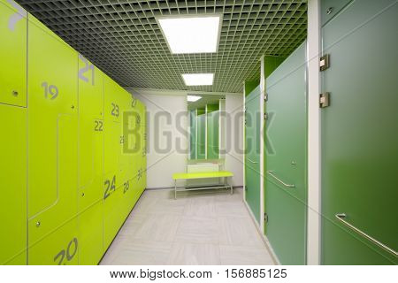 Empty bright modern cloakroom and Shower cabins in gym with lockers and mirror