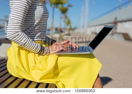 Woman sitting on bench outside and working on computer