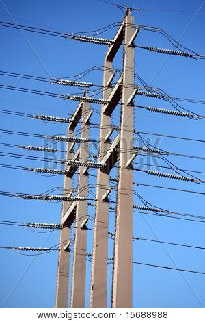 Power lines against bright blue sky