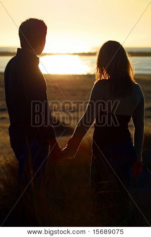 A young couple on the beach holding hands at sunset