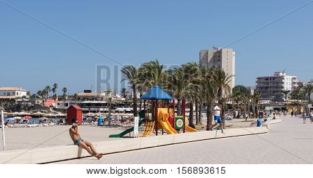 Xabia, Spain  - September 7, 2016: Man barechested sits talking on mobile near childrens playground  on beach esplanade  on Mediterranean Costa Blanca SpainSpain