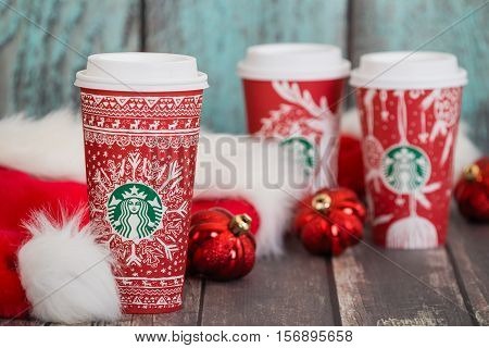 DALLAS TX - NOVEMBER 15 2016: Starbucks popular holiday beverage served in the new 2016 designed red holiday cup. Displayed with Christmas hats and ornaments on wooden rustic table.