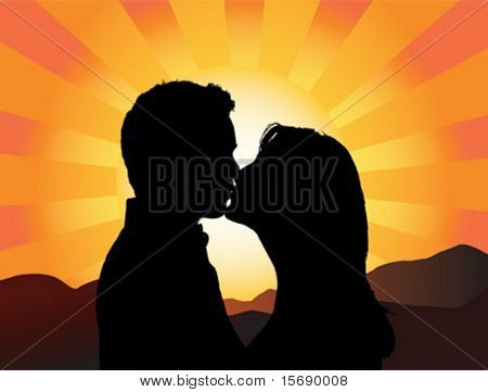 Silhouette of a young couple kissing with the sun setting behind them