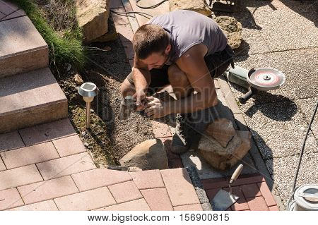 Man Build a dry wall in the garden. In the background various tools.