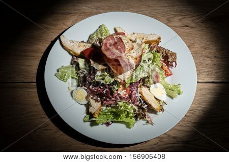 Caesar salad with croutons and bacon in the leaves of lettuce with cherry tomatoes served on a white plate on table
