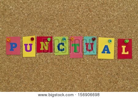 Punctual word written on colorful sticky notes pinned on cork board.