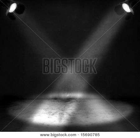 Two spotlights shining on a grungy floor in a room
