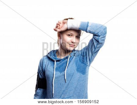 Teenage girl in blue sweatshirt, wearing phone armband, wiping sweat from her forehead. Beautiful young sportswoman, studio shot on white background, isolated.
