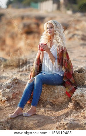 Blonde with long curly hair and grey eyes,dressed in a white shirt and blue jeans with holes on the shoulders draped a blanket,sitting on a big rock in a mountain area with a red Cup on the neck is a gold chain and locket,standing next to the basket