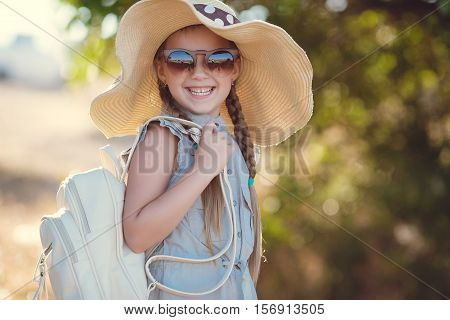 Young traveler girl in a straw hat with a large brim,dark sun glasses,light-blue summer suit,behind carries a blue backpack,hair braided in two pigtails posing outdoors in the summer in the countryside amid fields and green bushes