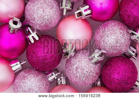 Christmas Time Background Some pale and bright pink sparkle and matte Christmas ball ornaments background