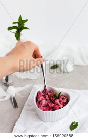 Beetroot Raita in White Dish with Female Hand Taking a Spoonful