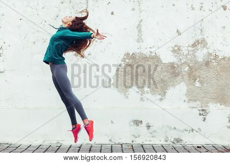 Fitness sport girl in fashion sportswear dancing hip hop in the street, outdoor sports, urban style