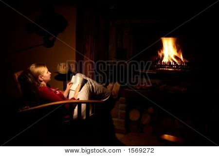Blonde Woman In Front Of The Fireplace.