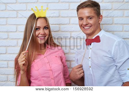 Close-up shot of extremely elated couple while standing over white background.  Funny couple holding paper bow-tie and crown, they are laughing while posing with paper accessories