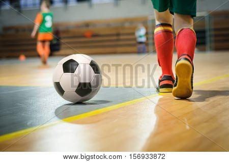 Football futsal training for children. Indoor soccer young player with a soccer ball in a sports hall. Sport background.