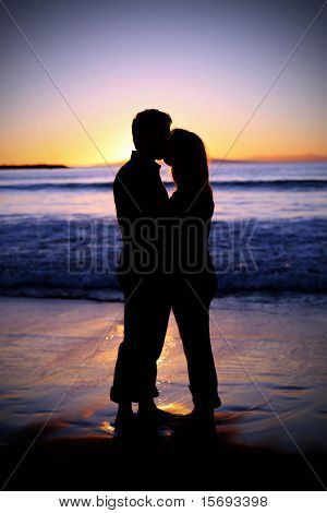 Silhouette of a young couple kissing at the beach with the sun sets behind them