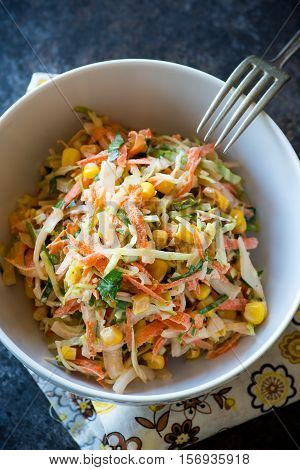 Fresh cabbage corn and carrot coleslaw salad in bowl mayonnaise dressing. Dark background top view closeup