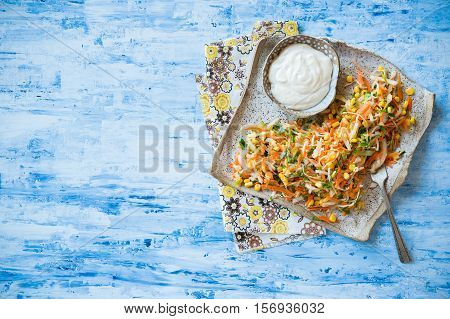 Fresh cabbage corn and carrot coleslaw salad on rustic plate mayonnaise dressing on side. Blue background top view copy space