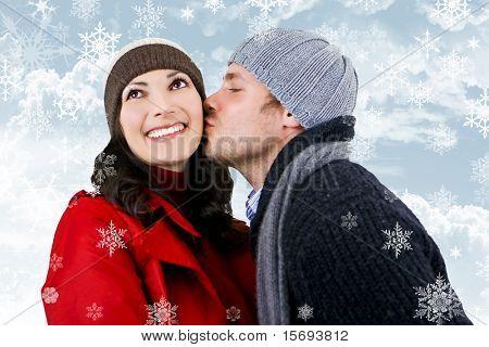 Una joven pareja de enamorados, rodeado de los copos de nieve