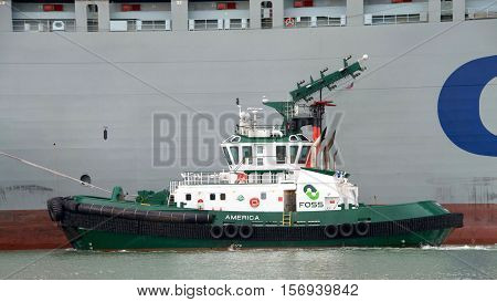 Oakland CA - November 15 2016: Tugboats are powerful for their size and strongly built. Tugboat AMERICA assisting cargo ship COSCO FORTUNE maneuver into the Port of Oakland.