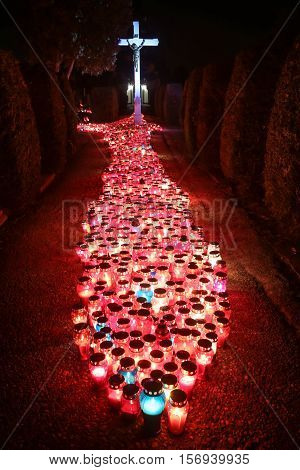 A night view of hundreds of candles lit for the deceased family members and friends in front of the cross at city cemetery on All Saints day in Velika Gorica Croatia.