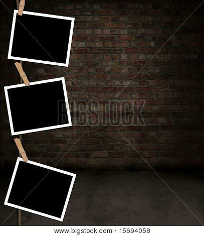 Blank photos hanging grungy brick room