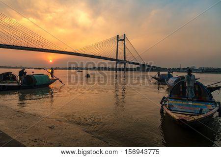 An oarsman wait for tourists to take on a boat ride on the river Hooghly near Vidyasagar bridge (setu) at sunset. Photograph taken at Princep ghat, Kolkata, India dated November 13, 2016.