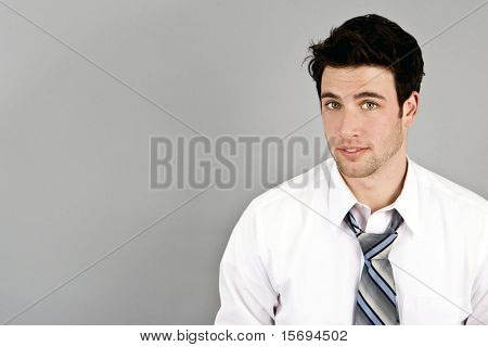 Handsome young businessman isolated on gray