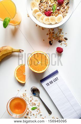 Breakfast with oatmeal and orange juice, to do list on white background top view