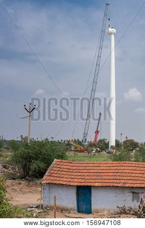 Dindigul India - October 24 2013: The long white supporting pole of a modern windmill is being erected by crane and men standing on top of the pole in rural area. Blue sky. Simple house in front. Green foliage.