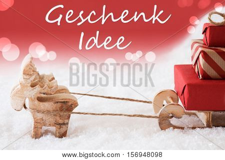 German Text Geschenk Idee Means Gift Idea. Moose Is Drawing A Sled With Red Gifts Or Presents In Snow. Christmas Card For Seasons Greetings. Red Christmassy Background With Bokeh Effect.
