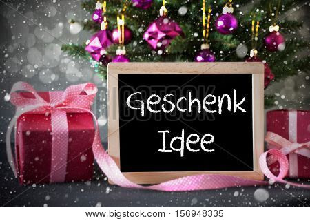 Chalkboard With German Text Geschenk Idee Means Gift Idea. Christmas Tree With Rose Quartz Balls, Snowflakes And Bokeh Effect. Gifts Or Presents In The Front Of Cement Background.