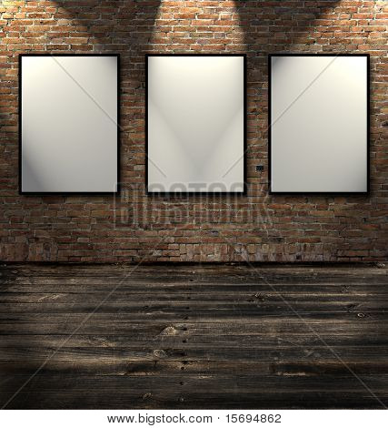 Three empty frames in a room against a white brick wall