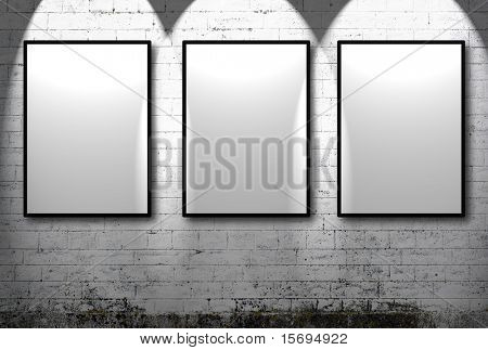 Three empty frames against a white brick wall